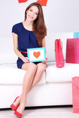 Beautiful young woman sitting on sofa with shopping bags on gray background — Stok fotoğraf