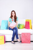 Beautiful young woman sitting on sofa with shopping bags and gift box on gray background — Stok fotoğraf