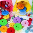 Stock Photo: Colorful buttons strewn from buckets close-up