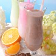 Milk shakes with fruits on table on light blue background — Stok fotoğraf