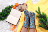 Composition with warm plaid, book,k and female legs, on color carpet background — Stock Photo