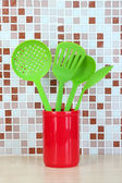 Cooking utensils in kitchen on table on mosaic tiles background — Stock Photo