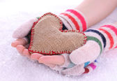Female hands in mittens with heart on snow background — Stockfoto
