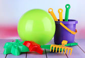 Bright ball and sandbox toys on table on bright background — Stock Photo