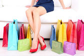 Female in red shoes sitting on sofa with shopping bags close up — Stok fotoğraf
