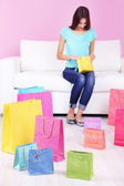 Beautiful young woman sitting on sofa with shopping bags on pink background — Stok fotoğraf
