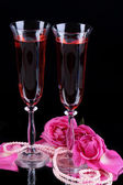 Composition with pink wine in glasses and roses isolated on black — Stock Photo