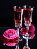 Composition with pink wine in glasses and roses on dark color background — Stock Photo
