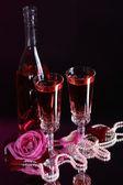Composition with pink wine in glasses, bottle and roses on dark color background — ストック写真