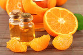 Tangerine essential oil and tangerines on grey bamboo mat — Stock Photo