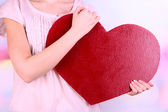 Female holding big red heart on bright background — ストック写真