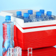 Traveling refrigerator with bottles of water and ice cubes, on blue background — Stock Photo #40204775