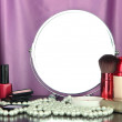 Round table mirror with cosmetics and chaplet on table on fabric background — Stock Photo #40206541