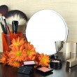 Round table mirror with cosmetics and flowers on table on wooden background — Stock Photo #40206575