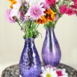 Wildflowers in glass vases on table on wooden background — Stock Photo
