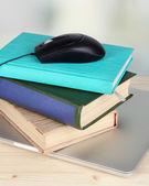 Computermuis op boeken en notitieblok op houten tafel op kamer achtergrond — Stockfoto