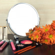 Round table mirror with cosmetics and flowers on table on wooden background — Stock Photo #40277941