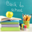 School supplies on table on blackboard background — Stock Photo