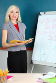 School teacher near whiteboard on blackboard background — Stock Photo