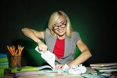 Méchant professeur assis à table sur fond coloré foncé — Photo