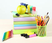School supplies on table on blackboard background — Foto Stock