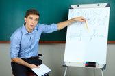 Young teacher sitting near chalkboard in school classroom — Stock Photo