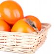 Stock Photo: Ripe persimmons in wicker basket isolated on white