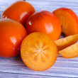 Stock Photo: Ripe persimmons on wooden background