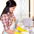 Beautiful young womwashing dishes in kitchen — Stock Photo #40281631