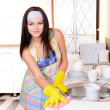 Beautiful young womcleans in kitchen — Stock Photo #40281637