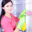 Beautiful young womwashing fridge in kitchen — Stock Photo #40281647