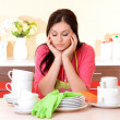 Beautiful young woman wipes clean utensils in kitchen — Stock Photo #40281649