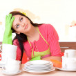 Beautiful young woman wipes clean utensils in kitchen — Stock Photo #40281673