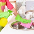 Beautiful young womcleans in kitchen — Stock Photo #40281701