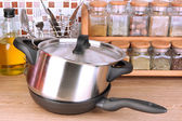 Pot and pan in kitchen on table on mosaic tiles background — Stock Photo