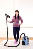 Beautiful young woman with vacuum cleaner in room — Stock Photo