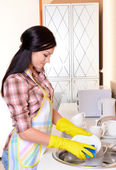 Beautiful young woman washing dishes in kitchen — Stok fotoğraf