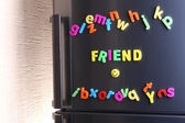 Word Friend spelled out using colorful magnetic letters on refrigerator — Stock Photo