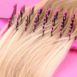 Stock Photo: Long blond hair with hairbrush on pink background