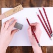 Hands holding pencil with art materials on wooden background — Stock Photo #40334013