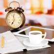 Tablet, newspaper, cup of coffee and alarm clock on wooden table — Stock Photo #40336331