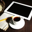 Tablet, newspaper, cup of coffee and alarm clock on wooden table — Stock Photo #40336359