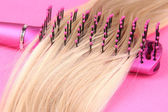 Long blond hair with hairbrush on pink background — Stock Photo