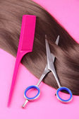 Long brown hair with comb and scissors on pink background — Stock Photo