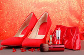 Beautiful red female shoes and cosmetics, on bright background — Stock Photo