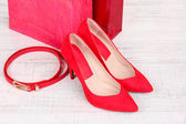 Beautiful red female shoes, belt and shop bags — Stok fotoğraf