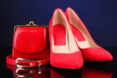 Beautiful red female shoes, purse and belt, on blue background — Stock Photo