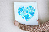Woman hanging up picture with heart from paper flowers — Stock Photo