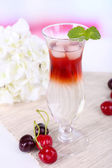 Glass of cocktail on table on light background — Stock Photo