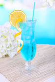 Glass of cocktail on table on light blue background — Stockfoto